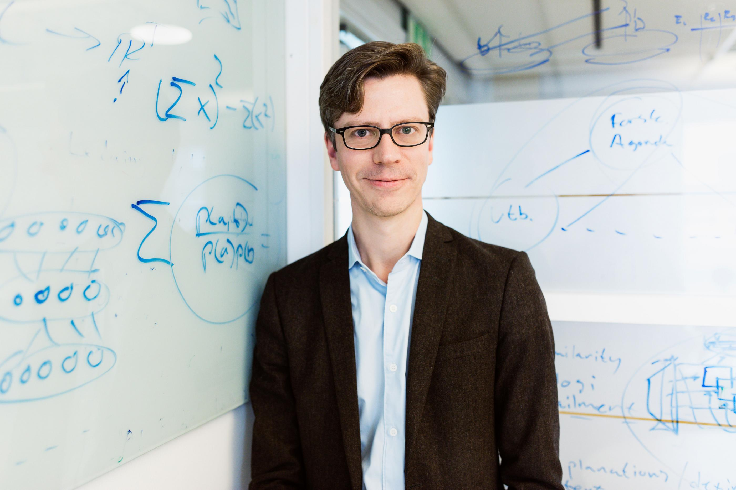 Daniel Gillblad in front of a whiteboard with mathematical calculations