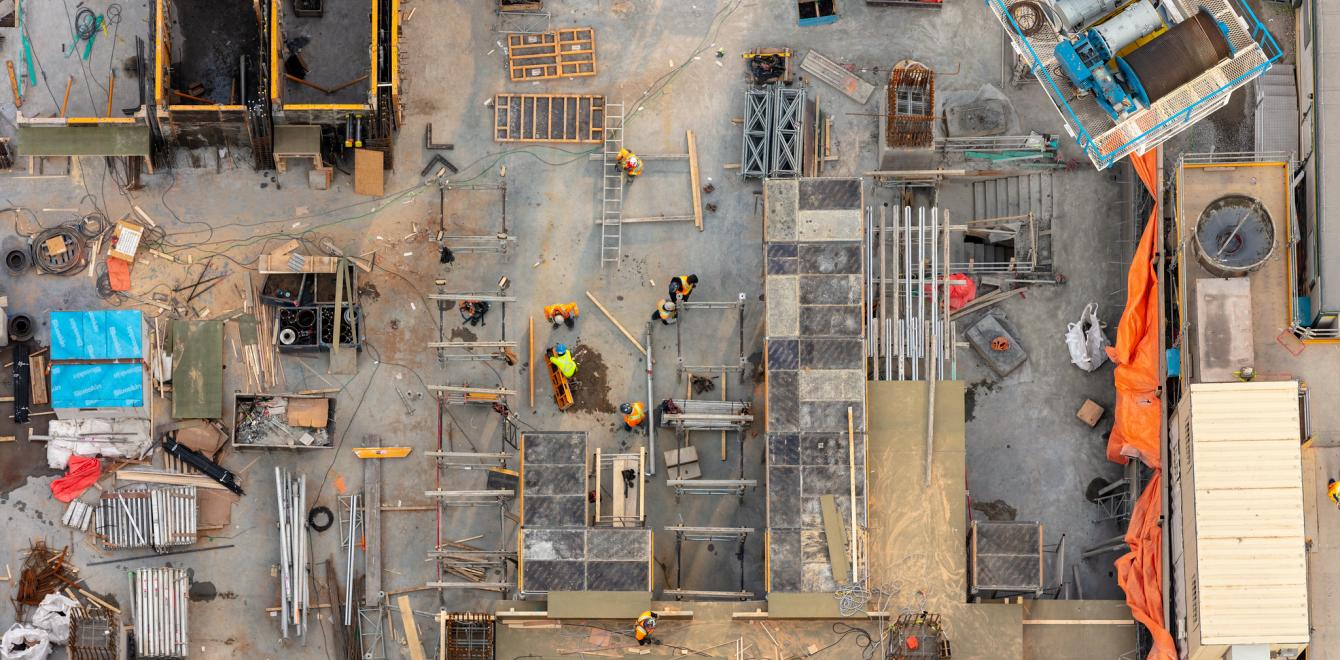 The image depicts an active construction site - including construction workers, tools, machines, buildings materials and pipes.