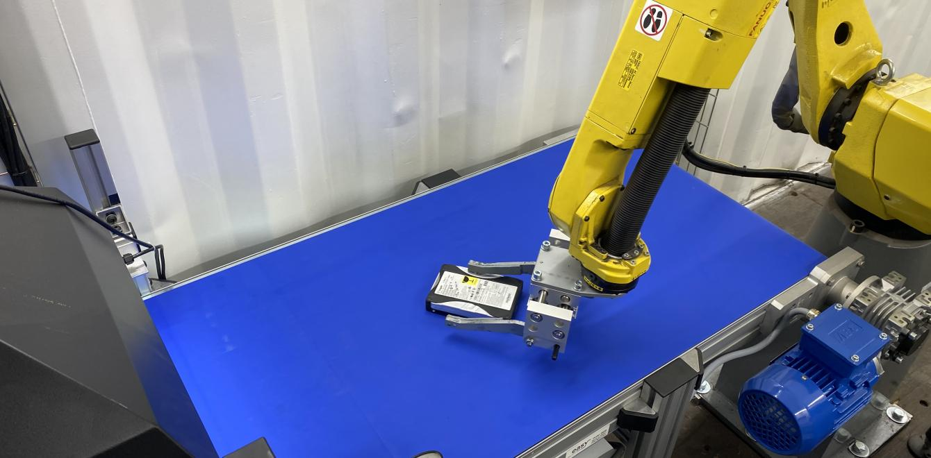 A scanned and analysed hard disk drive picked up by a robot arm